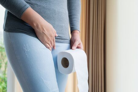 Disorder, Diarrhea, incontinence. Healthcare concept. Woman hand holding her crotch lower abdomen and tissue or toilet paper roll.
