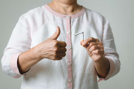 Quit smoking, no tobacco day, mother thumbs up with broken cigarette Reklamní fotografie