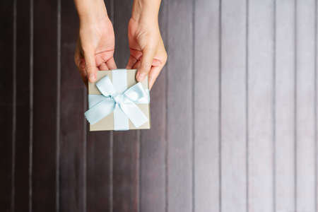 female hands holding a small gift wrapped with blue ribbon on wooden background Reklamní fotografie