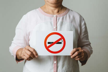 Quit smoking, no tobacco day, mother holding no smoking sign Reklamní fotografie