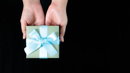 female hands holding a small gift wrapped with blue ribbon on black background