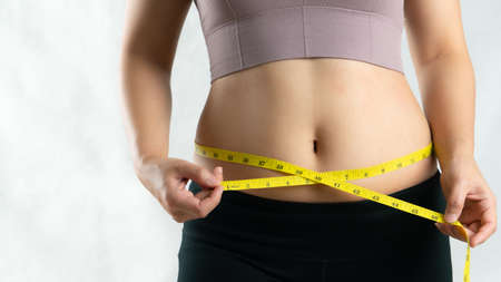young woman measuring her belly waist with measure tape, woman diet lifestyle concept Reklamní fotografie