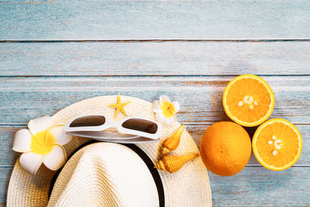 Beautiful summer holiday, Beach accessories, sunglasses, hat, oranges and shells on wooden backgrounds