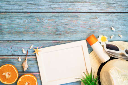 Beautiful summer holiday, Beach accessories, orange, sunglasses, hat and sunblock on wooden backgrounds