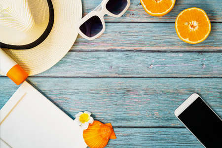 Beautiful summer holiday, Beach accessories, orange, sunglasses, hat, sunblockand smartphone on wooden backgrounds