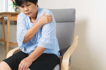 neck and shoulder pain, old woman suffering from neck and shoulder injury, health problem concept
