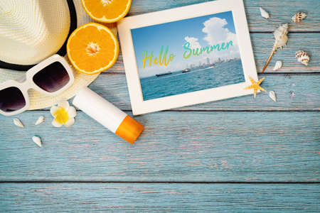 Beautiful summer holiday, Beach accessories, ornage, sunglasses, hat and sunblock on wooden backgrounds