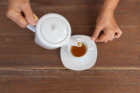 top view of a female pouring tea on wooden table
