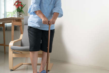 Knee pain of senior woman with stick, healthcare problem of senior concept