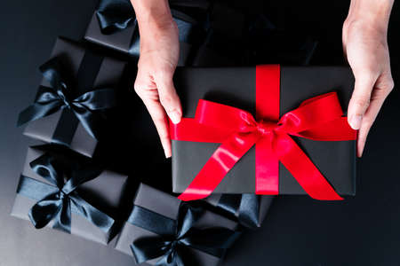black friday sale, woman hand give the gift box on black background