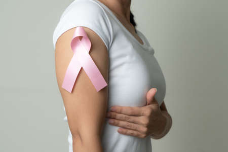pink badge ribbon on woman arm to support breast cancer cause. breast cancer awareness concept Zdjęcie Seryjne