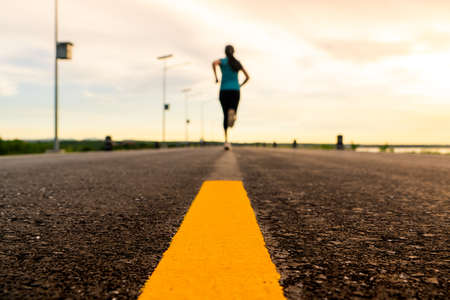 Athlete running on the road trail in sunset training for marathon and fitness. motion blur of woman exercising outdoors