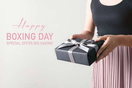 Boxing Day sale, young woman hold a gift box offer to receiver
