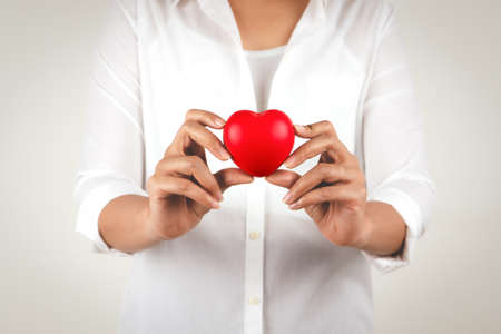 Healthcare concept of young woman hand holding red heart