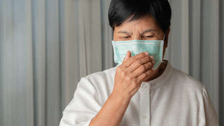 asian old woman wearing a face mask indoor coughing 版權商用圖片
