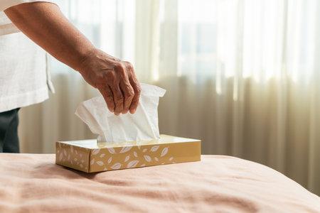 Senior women hand picking napkin/tissue paper from the tissue box