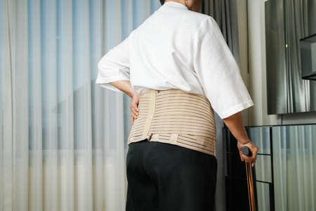 Senior back pain woman with walking stick at home 版權商用圖片