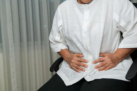 stomach pain of old woman at home, healthcare problem of senior concept 版權商用圖片