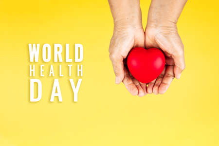 World health day concept Healthcare medical insurance with red heart on senior woman's hands support Banco de Imagens
