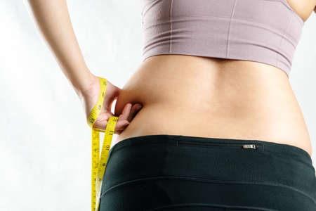 fat woman, fat belly, chubby, obese woman hand pinching on her excessive belly fat waist with measure tape, woman diet lifestyle concept - rear view