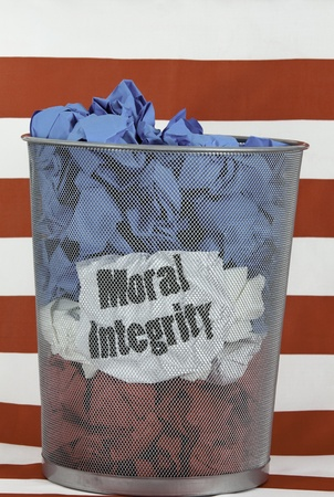 diplomats: Politics and Moral Integrity. Waste basket with wads of red, white, and blue paper, The words MORAL INTEGRITY show through the wastebasket. Red and white striped background.