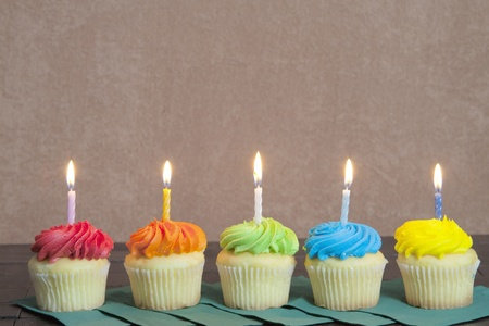 five objects: Five cupcakes with lit candles sitting in a row on green napkins for a party.