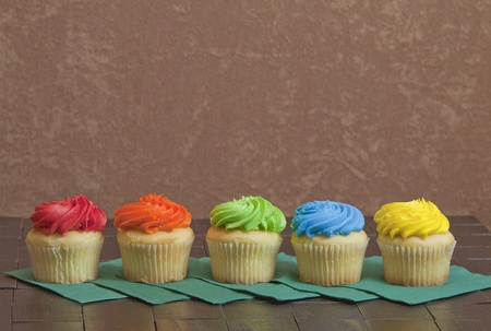 Five colorful cupcakes sitting in a row on green napkins with brown stucco background.