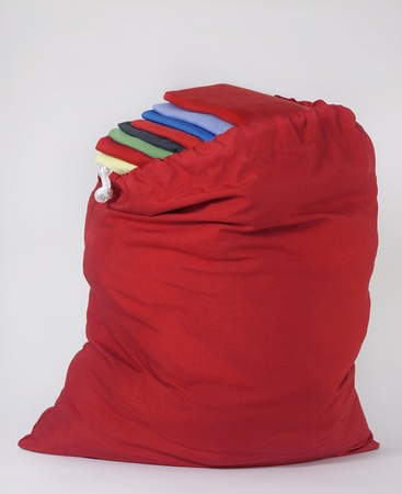 laundry: Red Laundry Bag with Bright Folded Shirts Piled on Each Other