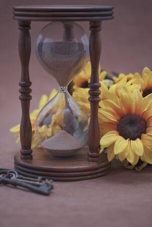 Hourglass, black-eyed susan, and skeleton keys on beige background  Selective focus