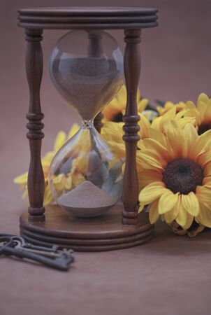 Hourglass, black-eyed susan, and skeleton keys on beige background  Selective focus  photo
