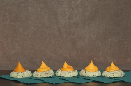pecans: Five Cookies with in a Row with orange icing sitting on green napkins against a brown stucco background Stock Photo