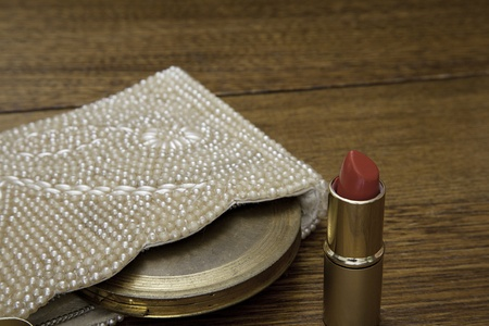 lipstick tube: 1920 pearl handbag with vintage powder compact and an open tube of red lipstick on dark oak dressing table