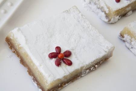 powdered sugar: Lemon Square Closeup with Red Candy Accent on White Serving Tray