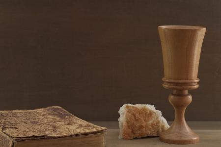 Bijbel, brood, houten kop op oude houten tafel