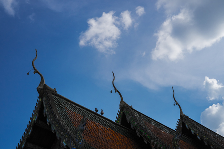 Thai temple roof with couple of bird and blue sky background