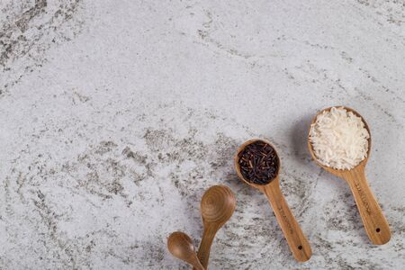 Jasmine rice and Rice berry in wooden spoons