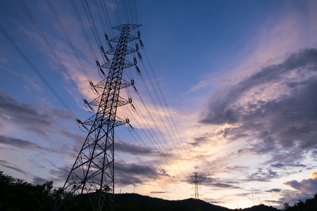 A silhouette electricity pylon and line pass through mountains, taken at the sunset Stock Photo