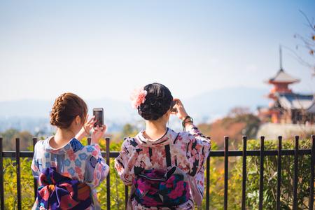 Kyoto, Japan-November 5,2017 : Two women in traditional Japan dress Yukata taking  photos of Kyoto cityscape from smartphone. Photo taken at Kiyomizu-dera.
