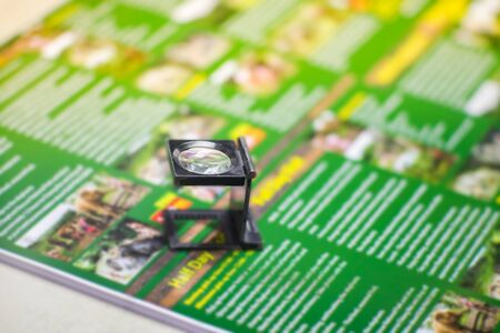 Black magnifying glass on colourfuk printed paper. Industrial printing process.
