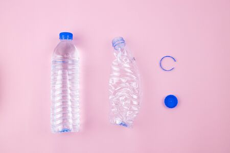 Full drinking water contained in transparent plastic bottle and empty crushed bottle preparing for recycling, plastic label removed, blue cap isolated. Flat lay set on pink colour background.