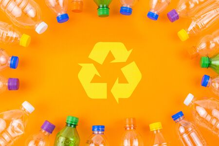 Collection of empty clean plastic bottles with various color caps arranged in rounded frame on orange colour background with recycling symbol.