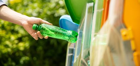 Close up shot, hand putting green empty plastic bottle into recycle bin. Panorama ratio. 写真素材