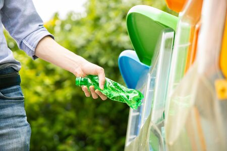 Asian male putting twisted green plastic bottle into recycle bin in park. 写真素材
