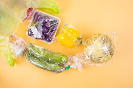 Plastic pollution concept. Piece of plastic wraps on globe after set of vegetables dumped out of big green plastic bag from grocery store. Close up shot, top-view on light orange background. Stock Photo