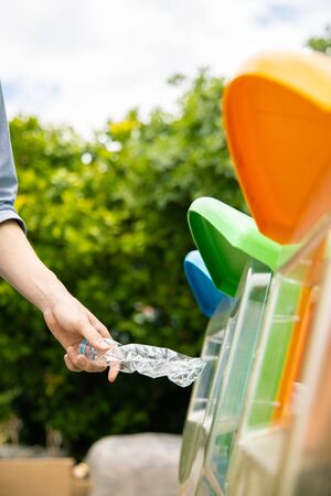 Man putting twisted plastic drinking water bottle into recycle bin in park, close up shot.