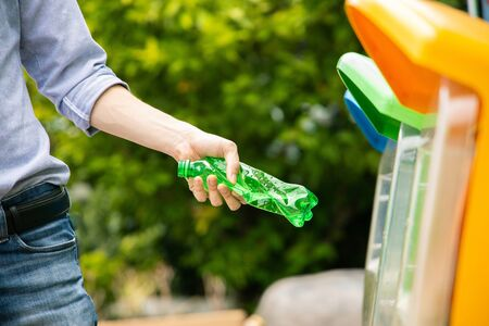 Male hand putting twisted empty plastic drinking water bottle into recycle bin.