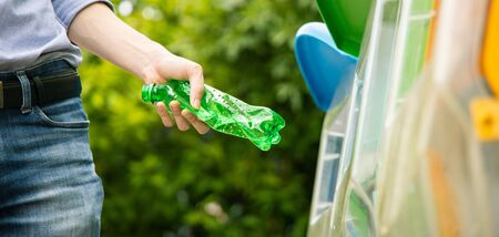 Panoramic photo of Asian male putting twisted green plastic bottle into recycle bin in park.