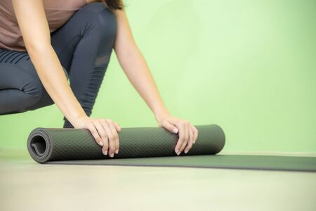 Young Asian woman concentrates on rolling black yoga mat after yoga class close up shot.
