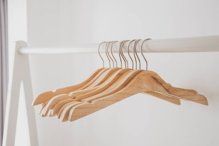 Wood hangers hang on bar with white clean background in open closet, easy and clean lifestyle concept.