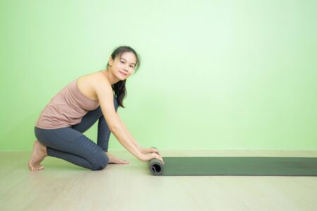 Young beautiful smiling Asian woman rolling yoga mat after finish yoga practicing in green wall studio, yoga class concept.